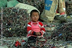 Computerschrott, Computerreste, Elektronikschrott in China. Kleinkind sitzt zwischen Computerschrott, Kabeln.